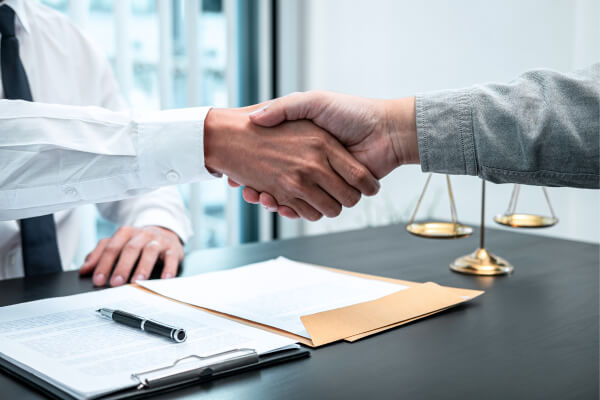 male lawyer shaking hands with client after good deal negotiation cooperation meeting courtroom 1 The Law office of John Vermon Moore